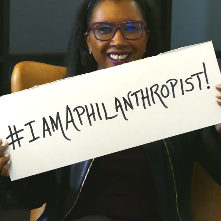 Woman holding I Am A Philanthropist sign