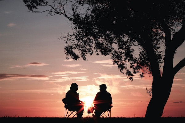 Two people talking in front of a sunset